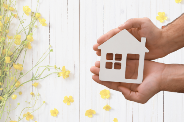 wood house in mans hands with yellow flowers